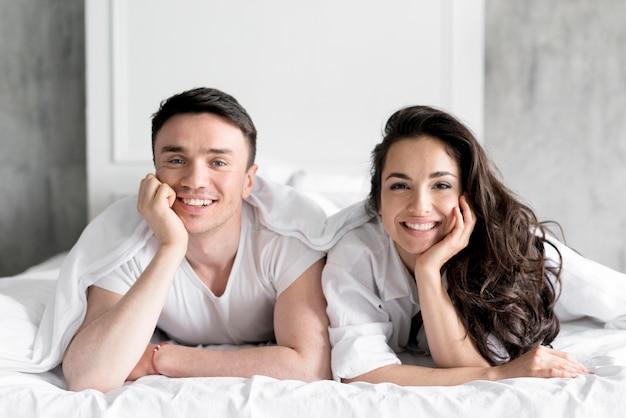 Vista frontale delle coppie che posano a letto