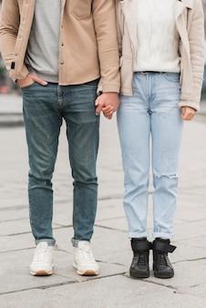 Vista frontale delle coppie che posano mentre tenendosi per mano