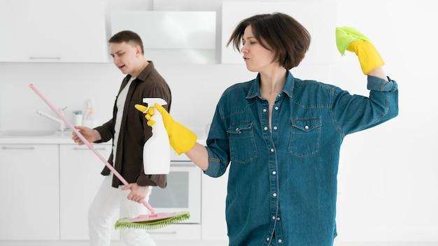 Vista frontale delle coppie che puliscono la casa