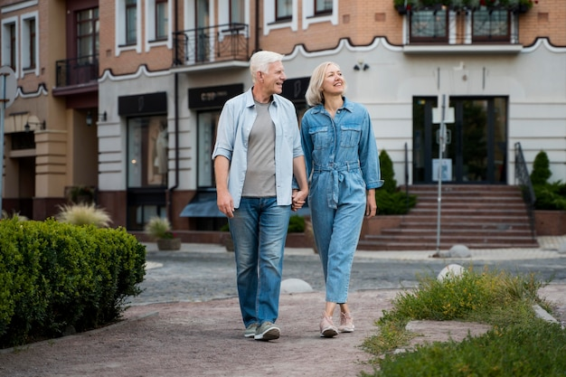 Vista frontale delle coppie senior abbracciate che godono il loro tempo nella città