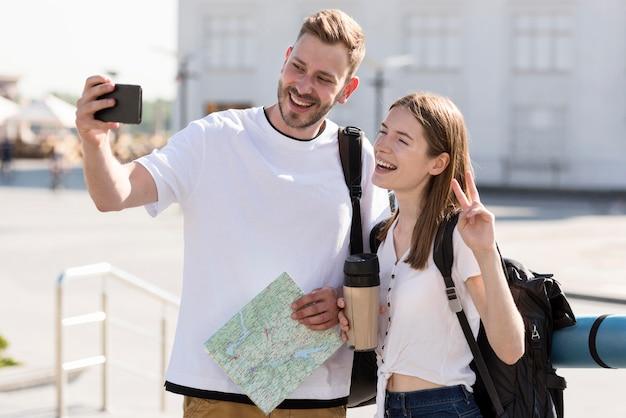 Vista frontale delle coppie turistiche all'aperto con gli zainhi e la mappa che prendono selfie