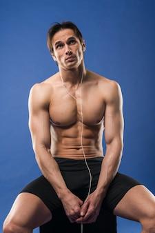 Vista frontale delle cuffie da portare dell'uomo muscoloso senza camicia