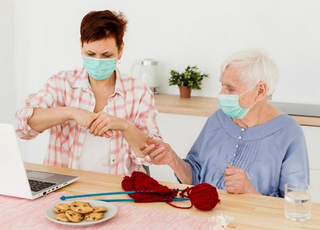 Vista frontale delle donne anziane che disinfettano le loro mani a casa