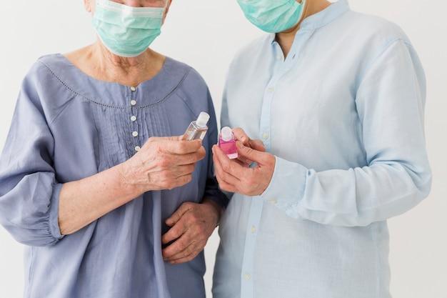 Vista frontale delle donne anziane con maschere mediche che tengono disinfettante per le mani