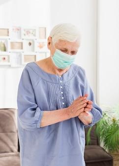 Vista frontale delle donne anziane con pregare maschera medica