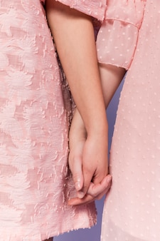 Vista frontale delle donne che si tengono per mano come segno di unità