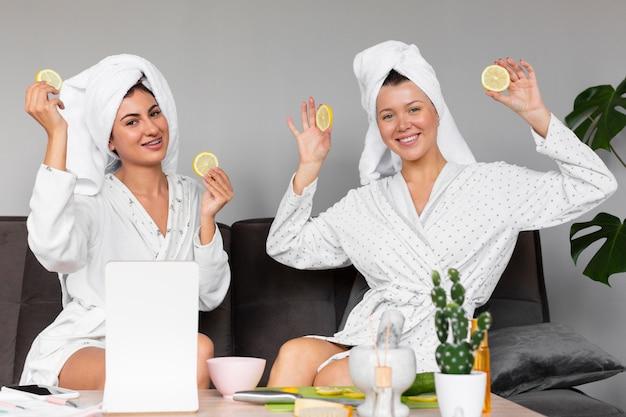 Vista frontale delle donne in accappatoi e asciugamani che tengono fette di limone