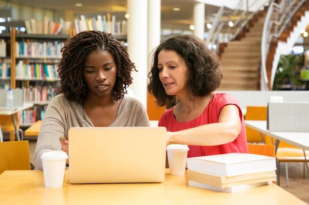 Vista frontale delle donne serie che si siedono alla tavola e che per mezzo del computer portatile