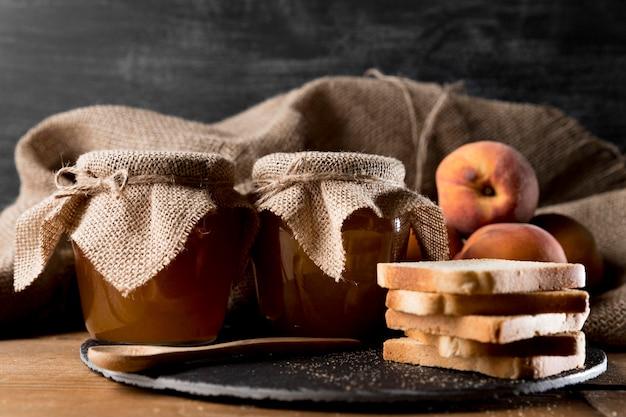 Vista frontale delle fette di pane con vasetti di marmellata