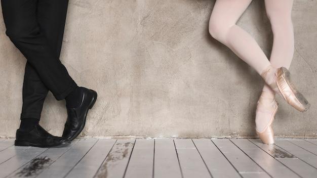 Vista frontale delle gambe della ballerina e uomo elegante
