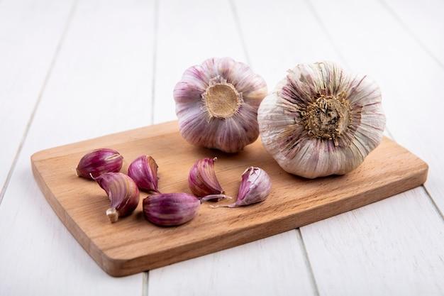 Vista frontale delle lampadine e dei chiodi di garofano di aglio sul tagliere su superficie di legno