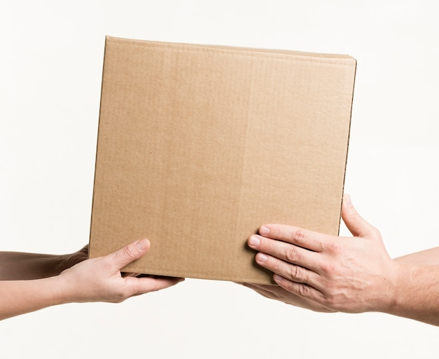 Vista frontale delle mani che tengono cartone