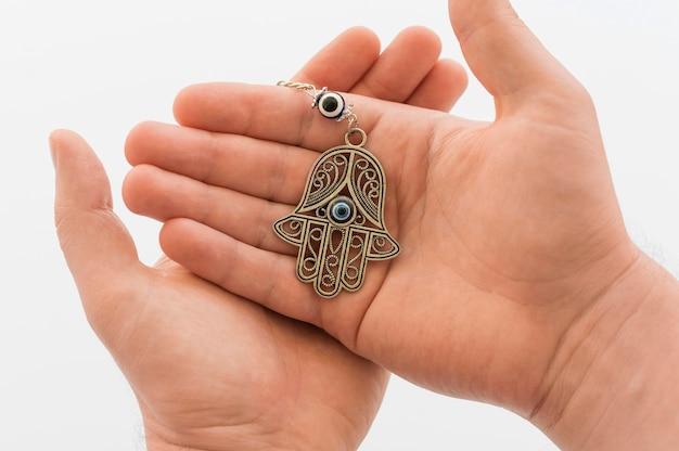 Vista frontale delle mani che tengono il pendente di hamsa