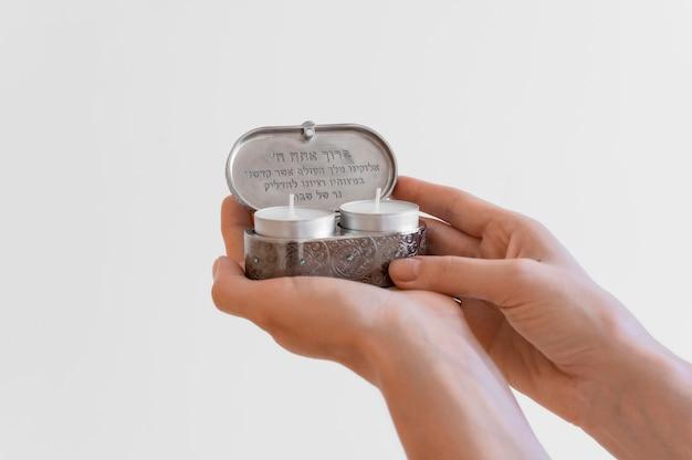 Vista frontale delle mani che tengono le candele della luce del tè per la preghiera