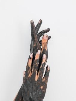 Vista frontale delle mani coperte di vernice nera