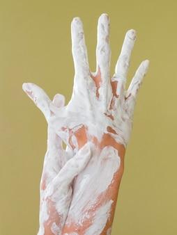 Vista frontale delle mani dipinte con vernice bianca