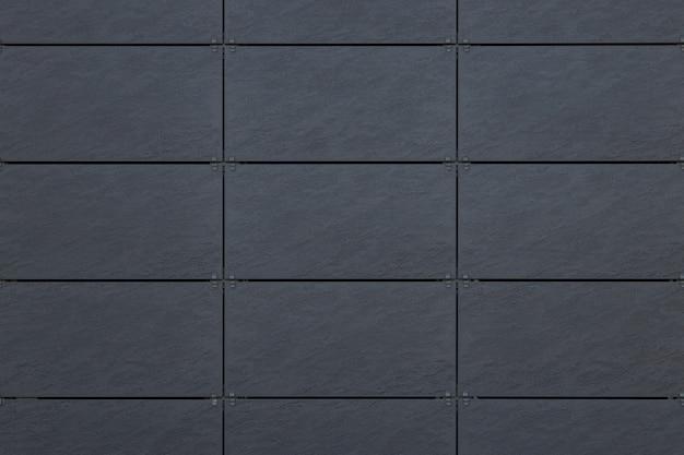 Vista frontale delle mattonelle grige sulla parete con la linea di griglia scura per struttura
