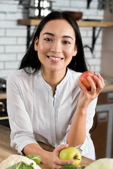 Vista frontale delle mele sorridenti della holding della donna che esaminano macchina fotografica