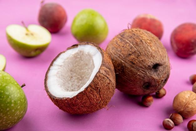 Vista frontale delle noci di cocco fresche con le pesche verdi delle mele su superficie rosa