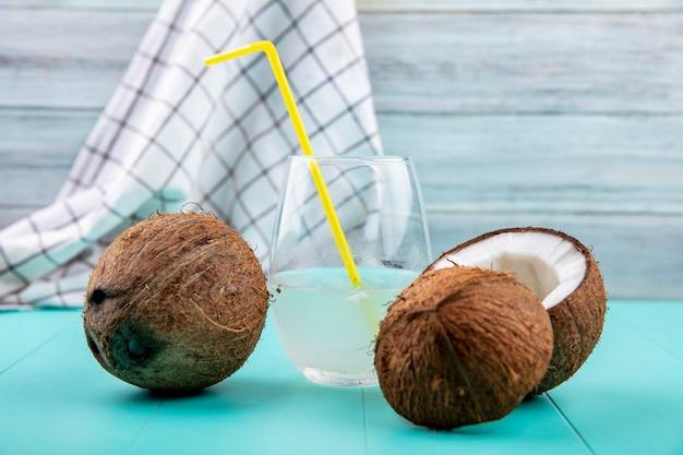 Vista frontale delle noci di cocco fresche con un bicchiere d'acqua sulla tovaglia e sulla superficie di legno grigia