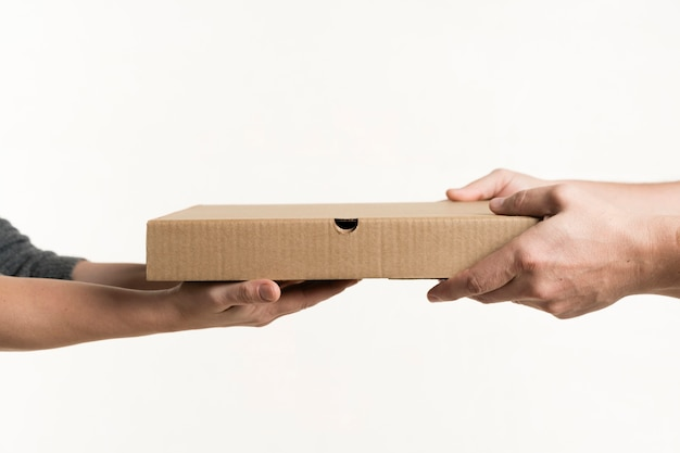 Vista frontale delle paia delle mani che tengono il contenitore di pizza