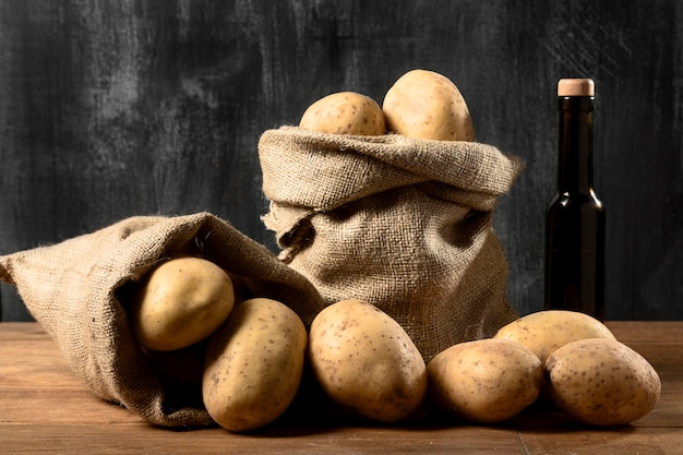 Vista frontale delle patate nel sacco di iuta con bottiglia di olio