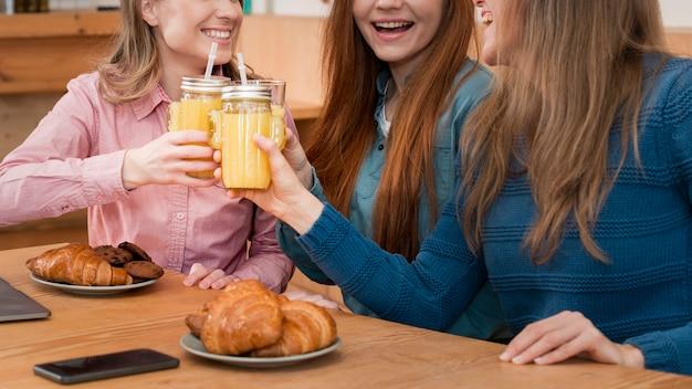 Vista frontale delle ragazze che si siedono al tavolo