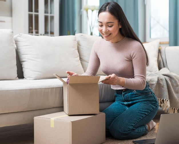 Vista frontale delle scatole di apertura della donna dopo aver ordinato online