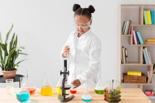 Vista frontale dello scienziato della ragazza in camice da laboratorio con pozioni