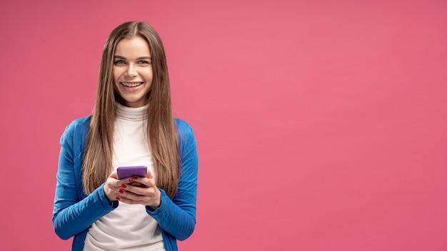 Vista frontale dello smartphone della tenuta della donna di smiley