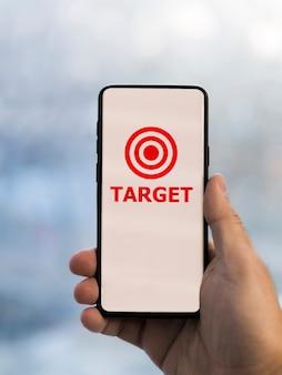 Vista frontale dello smartphone tenuto in mano con l'obiettivo