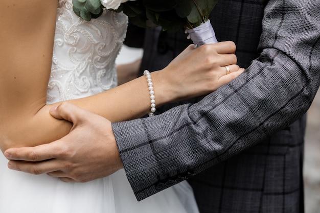 Vista frontale dello sposo che tiene la tenera mano di una sposa con un braccialetto di perle