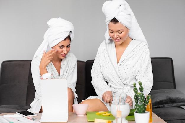 Vista frontale di amiche in accappatoi e asciugamano che applicano prodotti di bellezza