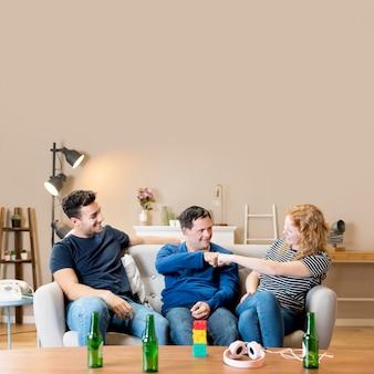 Vista frontale di amici a casa a bere una birra