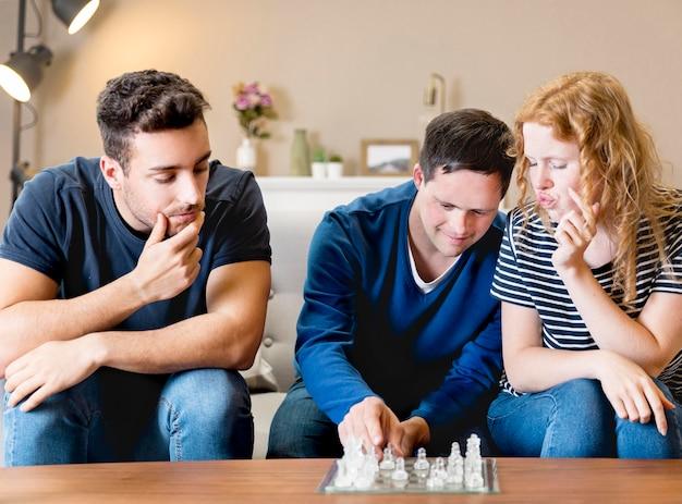 Vista frontale di amici che giocano a scacchi