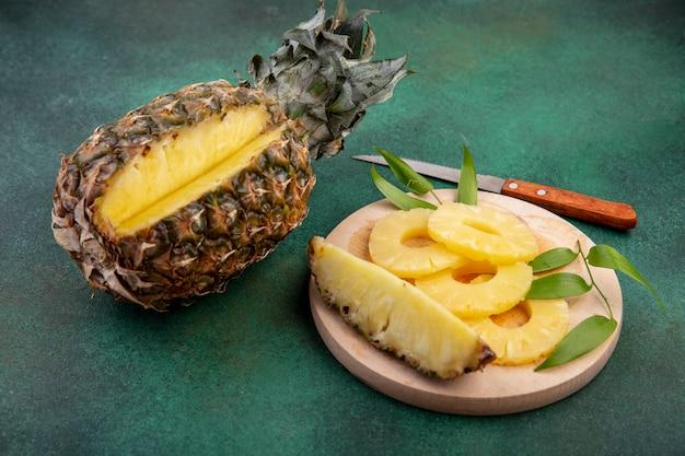 Vista frontale di ananas con un pezzo tagliato da fette di frutta e ananas intero sul tagliere con coltello sulla superficie verde