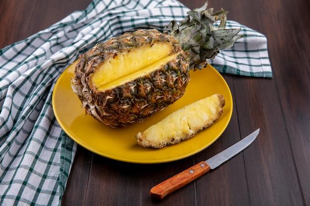 Vista frontale di ananas con un pezzo tagliato da tutta la frutta nel piatto sul panno plaid con coltello su superficie di legno
