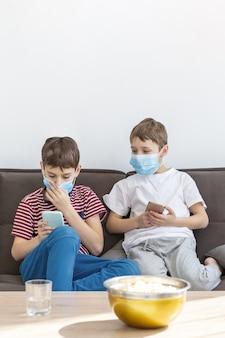 Vista frontale di bambini con maschere mediche che giocano su smartphone