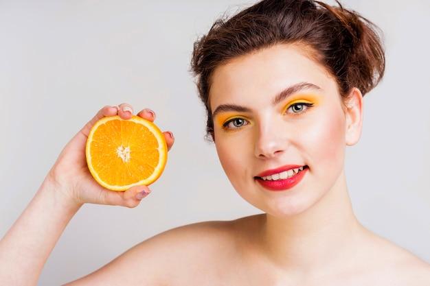 Vista frontale di bella donna con l'arancia