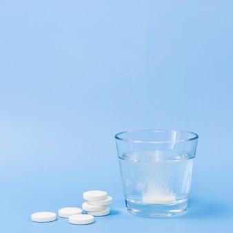 Vista frontale di bicchiere d'acqua con lo spazio effervescente della compressa e della copia
