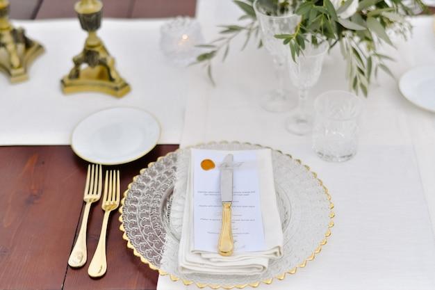 Vista frontale di bicchieri e posate dorate servite sul tavolo di legno e targhetta stampata per gli ospiti e tovaglioli in tessuto bianco