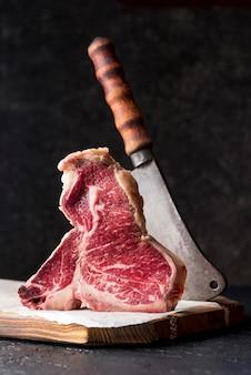Vista frontale di carne con mannaia