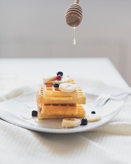 Vista frontale di cialde e cucchiaio di miele