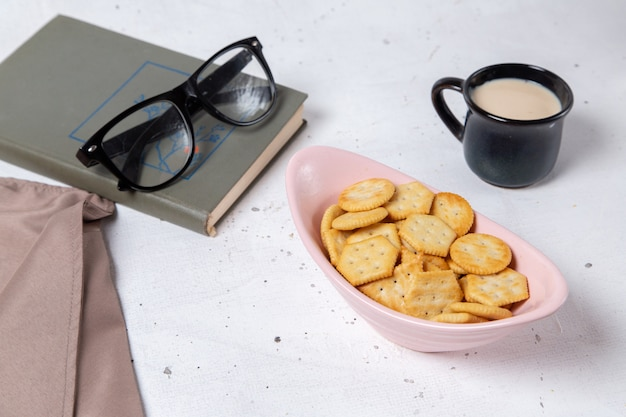 Vista frontale di cracker e patatine all'interno del piatto rosa con occhiali da sole e tazza di latte sulla scrivania leggera