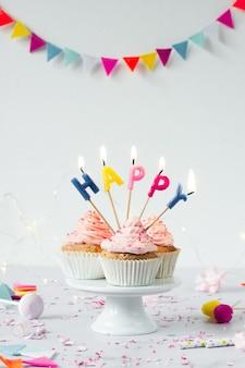 Vista frontale di cupcakes di compleanno con candele accese