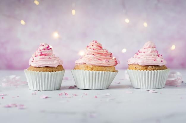 Vista frontale di cupcakes di compleanno con glassa e spruzza