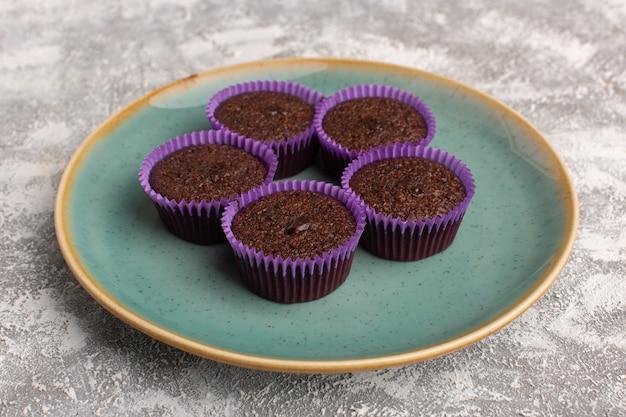 Vista frontale di deliziosi brownies all'interno del piatto verde sulla superficie della luce