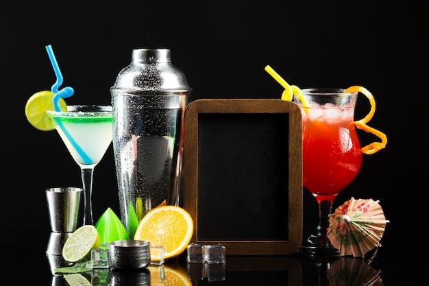 Vista frontale di diversi cocktail con shaker e lavagna