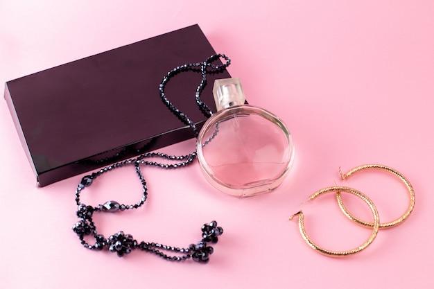 Vista frontale di elegante fragranza con collana e confezione regalo nera sulla superficie rosa