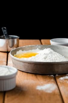 Vista frontale di farina e dell'uovo sulla tavola di legno